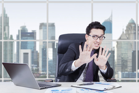 scolded: Caucasian manager with afraid expression try to hold something with his hands in the office