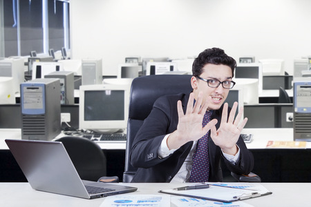 scolded: Young businessman with scared expression working in the office with laptop and business chart Stock Photo
