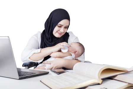 nursing bottle: Multitasking woman nursing her baby with milk from bottle while doing her job with laptop and book Stock Photo