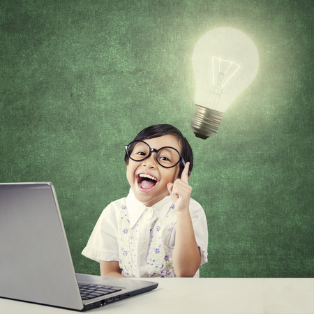 asia children: Female kindergarten student get idea and pointing at a bright lamp with laptop on the table
