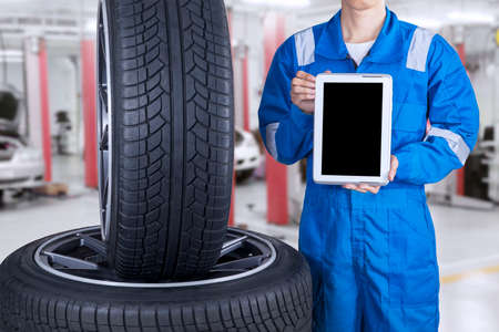 auto service: Male mechanic with blue uniform showing empty tablet screen near the tires, shot at workshop