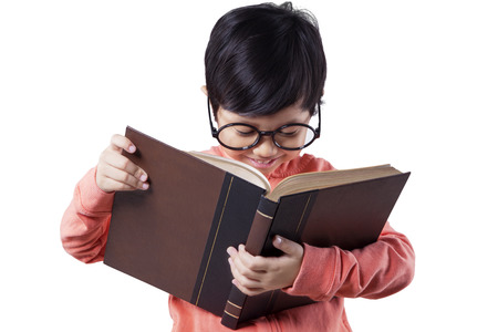 textbook: Pretty kindergarten student wearing glasses and reading a textbook, isolated on white background Stock Photo