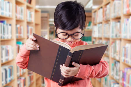 kid book: Portrait of adorable elementary school student with casual clothes, standing in the library while reading a book