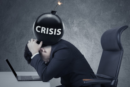 financial burden: Depressed businessman working with laptop with a bomb of economy crisis on his head
