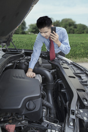businessman waiting call: Portrait of male entrepreneur looking at the broken machine car while calling help