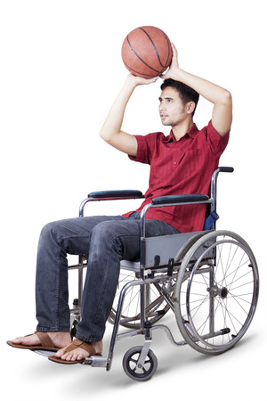 wheelchair: Young man sitting on wheelchair and try to play basketball, isolated on white background Stock Photo