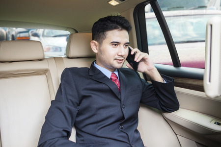 detras de: Retrato de joven hombre de negocios sentado en el asiento trasero del coche y hablando por teléfono