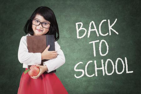 mignonne petite fille: Belle petite fille tenant un livre et la pomme de retour � l'�cole