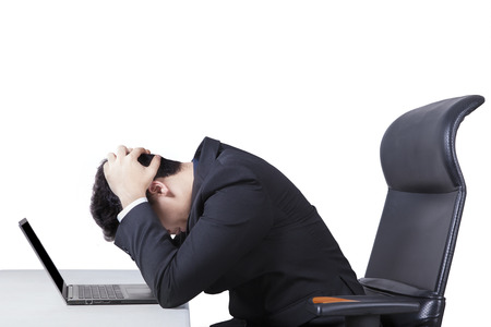 Portrait of stressful male worker sitting on office chair while holding his head with a laptop on desk, isolated on white Banque d'images