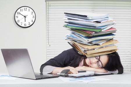 Jeune travailleuse dormir dans le bureau avec un ordinateur portable sur le bureau et les documents d'affaires sur la tête Banque d'images