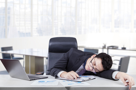 young worker: Male caucasian worker wearing glasses in office and sleeping on desk with laptop and paperworks