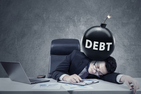 debt management: Portrait of caucasian worker sleeping on desk with laptop and a bomb of debt. Concept of financial crisis