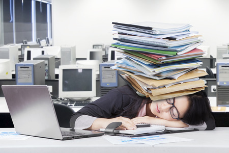 secretary: Young woman napping on desk with business documents over head. Shot at workplace Stock Photo