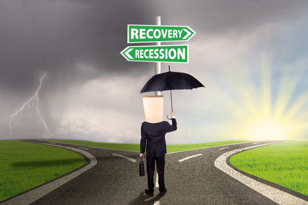 road to recovery: Worker with cardboard head and umbrella, standing on the road while looking at signpost directing at the road to recovery or recession financial