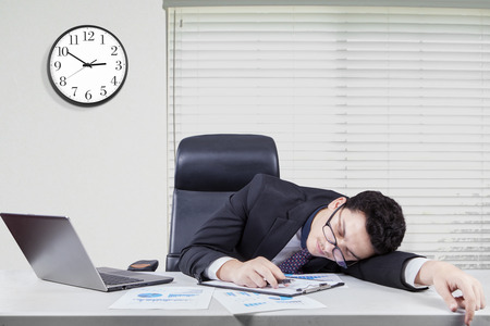 office wall: Portrait of caucasian worker with formal suit sleeping on desk in the office with a clock on the wall