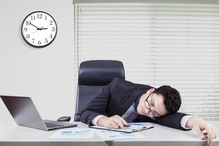 agotado: Retrato de caucásicos trabajador con traje formal duerme en el escritorio en la oficina con un reloj en la pared