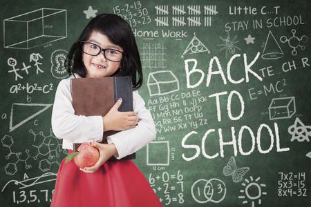 La niña sostiene un libro y la manzana volver a la escuela en el aula Foto de archivo