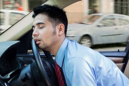 Exhausted young businessman sleeping in the car while driving the car on the road Stock Photo