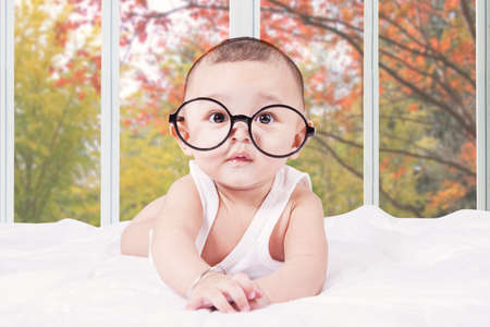 model male: Portrait of male baby looking at the camera while lying on bedroom and wearing a round glasses Stock Photo