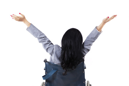paraplegico: Mujer joven discapacitado que se sienta en una silla de ruedas y levantar las manos en el estudio, aislado en blanco Foto de archivo