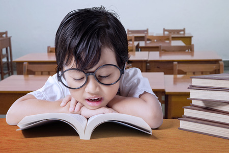 kid book: Cute girl wearing glasses and reading textbooks on the table in the classroom