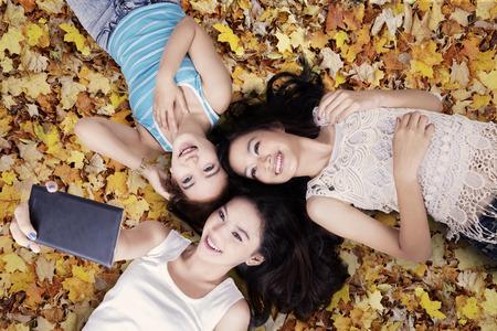 Perspectiva única de tres chicas adolescentes que toman el cuadro con el teléfono inteligente mientras se está acostado en las hojas de otoño Foto de archivo - 42870880