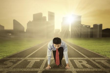 atleta corriendo: Joven empresario con traje formal listo para correr en la pista, tiro al aire libre Foto de archivo