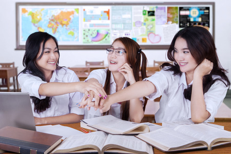 joining hands: Three female high school students studying in the classroom and joining hands together