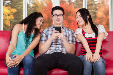 indian culture: Two mixed race girls sitting on the sofa while looking at the smartphone on the guy hands Stock Photo