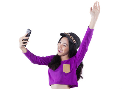 sorprendido: Portrait of trendy teenage girl holding cellphone and celebrate her victory in the studio, isolated on white
