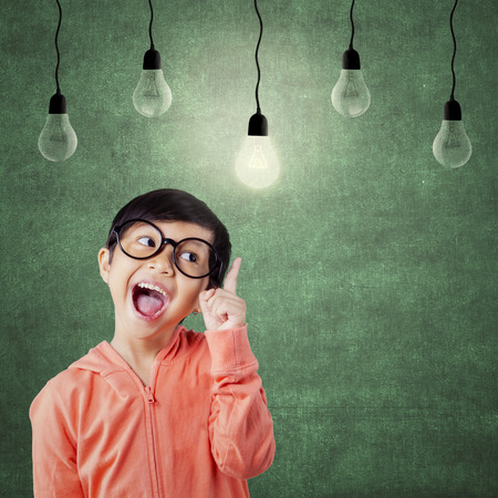 idea bulb: Portrait of attractive female student pointing at bright lamp in the class while wearing glasses Stock Photo