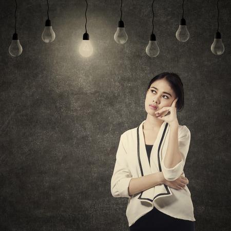 working class: Asian business woman thinking under lightbulb in class
