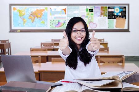 High school student: Portrait of cheerful high school student smiling on the camera while studying and showing thumbs up in the classroom