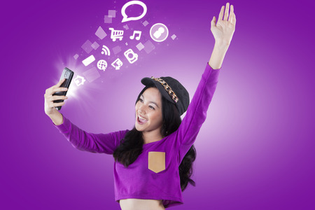 accessing: Cheerful modern teenage girl accessing internet and social media with a smartphone, shot with purple background Stock Photo