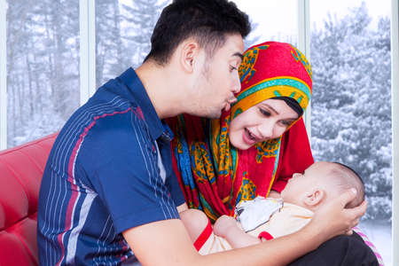 muslim baby: Portrait of two young muslim parents playing with their baby on sofa at home, shot with winter background on the window Stock Photo