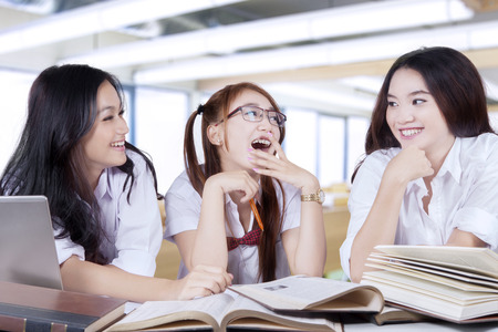 study group: Portrait of three excited female students back to school and studying in the classroom while talking and laughing together