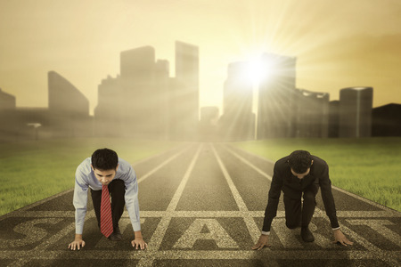 competencia: Concepto de la competencia de negocios con dos hombres de negocios que se arrodilla en la línea de salida y listo para competir