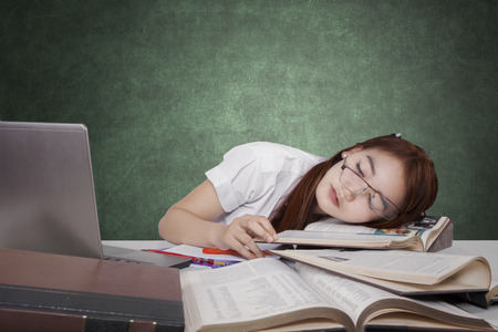 Study Desk: Brunette female high school student sleeping in the class above the book with laptop on the table Stock Photo