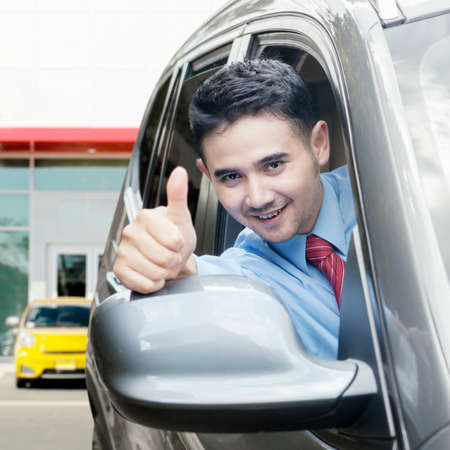 asia people: Successful businessman driving new car and showing thumb up on the camera Stock Photo