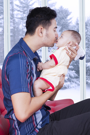 family life: Three months baby kissed by his father on the sofa near the window at home