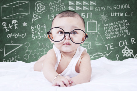 Cute male baby looking on the camera while wearing glasses, shot with a doodles background on the blackboard Imagens