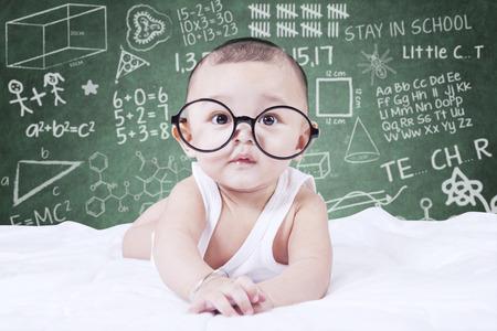 Leuke mannelijke baby die op de camera tijdens het dragen van een bril, geschoten met een doodles achtergrond op het bord