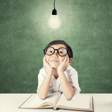 lamp: Lovely female student sitting under bright light bulb in the classroom with a book on the table
