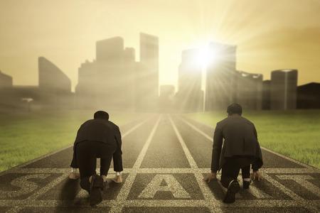 negocio: Vista trasera de dos trabajadores el uso de traje formal y de rodillas en la línea de salida para competir