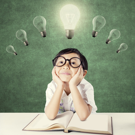 教育: 漂亮的女小學生有在桌子上一本教科書,想著主意而抬頭看著明亮的燈泡