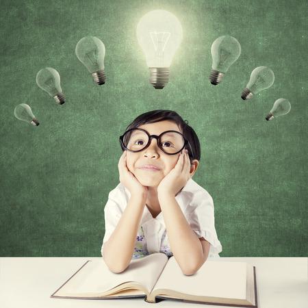 education: Attractive female élève de l'école élémentaire avec un manuel sur la table, pensant idée en regardant ampoule lumineuse