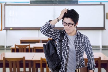 confundido: Retrato de estudiante de colegio masculino de pie en la clase y se ve confundido, libro en libros y mochila Foto de archivo