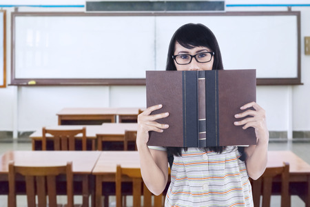 textbook: Young high school student standing in the classroom while holding a textbook looking at the camera Stock Photo