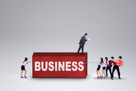 hurdle: Group of young entrepreneurs collaborate to move a business hurdle Stock Photo