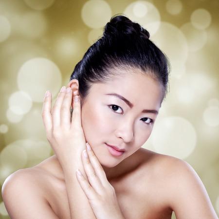 černé vlasy: Krásná čínská dívka s černými vlasy a krásy dokonalou pleť při pohledu na fotoaparát proti rozostření světlé pozadí